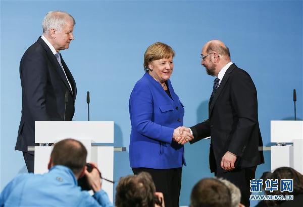1月12日,在德国首都柏林的社民党总部,德国总理、基民盟主席默克尔(中)和社民党主席舒尔茨(右)在新闻发布会后握手。.j