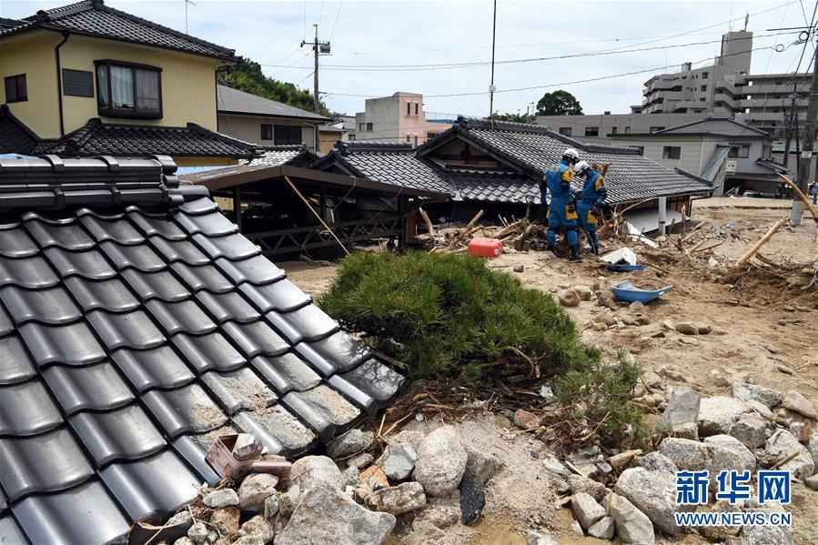 7月11日,在日本广岛吴市天应町地区,警察挖掘被泥石流淹没的民居。.jpg